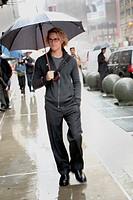 Caucasian man walking in rain with umbrella