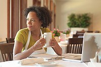 African American woman sitting at restaurant table with paperwork
