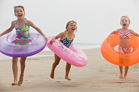 Caucasian girls in inflatable rings on beach
