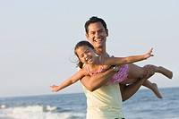 Father swinging daughter on beach