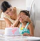 Mother covering daughter´s eyes near birthday cake