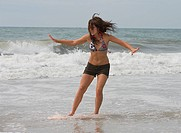 Teen girl skim boarding.