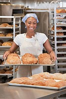 African American baker carrying tray of bread in bakery