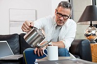 Caucasian pouring tea into coffee cup