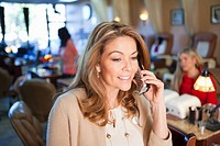 Hispanic business owner using telephone in beauty salon