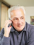 Germany, Munich, Senior man talking on mobile phone