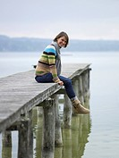 Germany, Munich, Mature woman sitting on jetty near lake, smiling, portrait