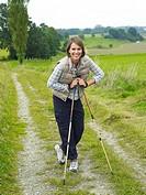 Germany, Munich, Mature woman nordic walking, smiling, portrait