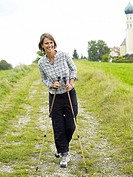 Germany, Munich, Mature woman nordic walking, smiling, portrait