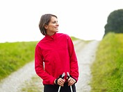 Germany, Munich, Mature woman nordic walking, smiling