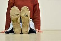 woman sitting on floor, wearing worn out sneakers