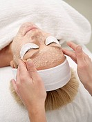 Mature woman receiving facial treatment, close up