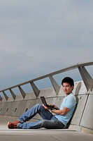 Young man sitting on ground working on laptop