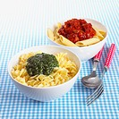 Bowl of penne with tomato sauce, bowl of fusilli pasta with pesto sauce, cutlery