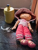Abandoned doll in an empty house besides a leaking bleach bottle