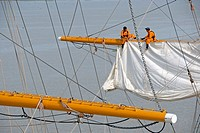 Men repairing a sail of the three-masted sailboat on Guayas river, used as a training ship for Ecuadorian Navy cadets, Guayaquil, Ecuador