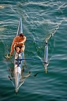 Man paddles outrigger canoe
