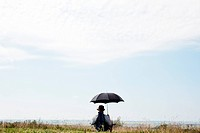 Man sitting under umbrella in field