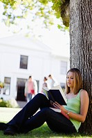 Student reading in grass on campus