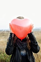 Girl holding heart_shaped balloon