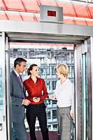 Business people riding elevator