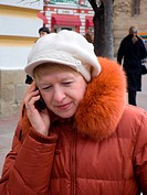 The woman, talks to phone in the street.
