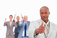 Salesman with team behind him giving approval against a white background