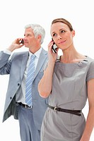 Close_up of a woman making a call with a white hair businessman in background