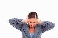 Close up of irritated tradeswoman covering her ears against a white background