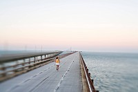 Woman Running on Bridge Over Ocean, Rear View, Florida Keys, USA