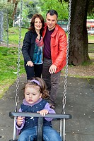 Father and mother pushing daughter on a swing