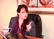 Pretty Businesswoman Sitting at Desk in Office