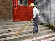 Street sweeper cleaning up red fireworks paper with a home made broom in Fuli near Yangshuo China
