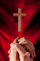 Human hand praying in front of wooden cross