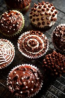 Close up of chocolate cupcakes decorated with frosting.