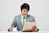 Businessman Reading Newspaper And Coffee Cup On Desk