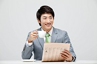 Businessman Reading Newspaper And Holding Coffee Cup