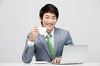 Businessman Sitting At The Desk Holding Coffee Cup And Using Laptop