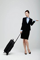 Asian Businesswoman Standing With Luggage Presenting