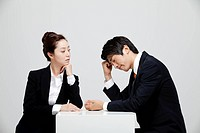 Asian Businesswoman Looking At Depressed Businessman