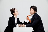 Asian Businesswoman Holding Tie Of Businessman At Desk Facing Each Other