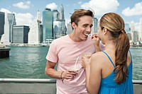 Couple eating ice cream in front of Manhattan skyline, New York City, USA