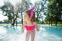 Girl 3_4 in tulle skirt at edge of swimming pool