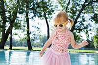 Girl 3_4 wearing costume and sunglasses playing at pool