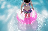 Girl 3-4 playing in water with inflatable ring (thumbnail)