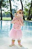Girl 3_4 wearing costume and sunglasses wading in water