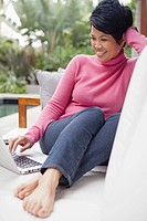Woman using laptop on garden sofa