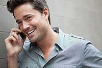 Portrait of smiling man talking on cell phone (thumbnail)