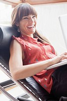 Portrait of smiling woman in armchair using laptop