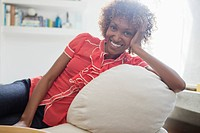 Portrait of smiling woman leaning on sofa
